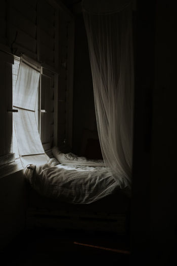 White curtain hanging on bed at home