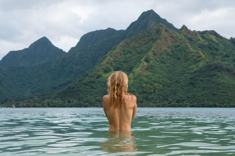 Rear view of shirtless woman in lake