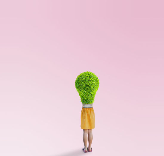 Woman standing against pink background