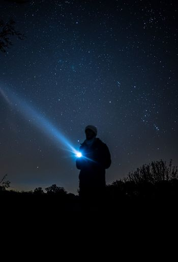 Silhouette young man holding flashlight while standing on field against star field at night