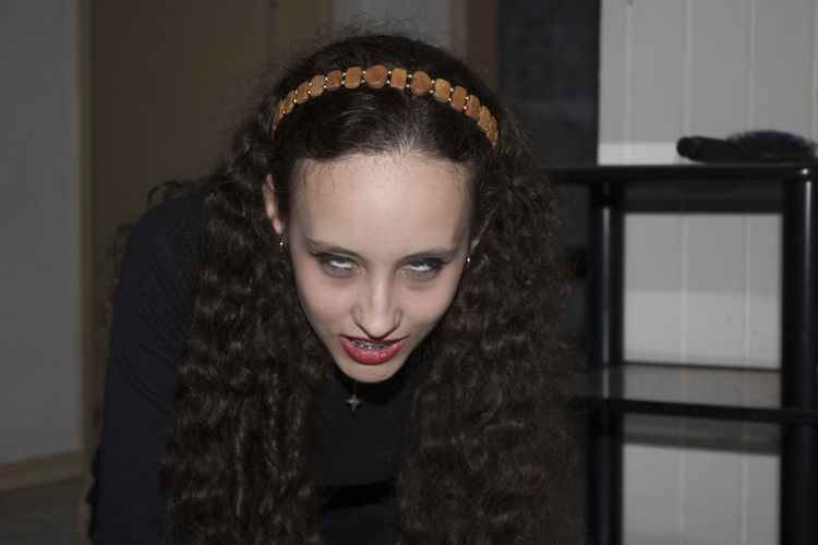 Young woman with spooky eyes kneeling at home