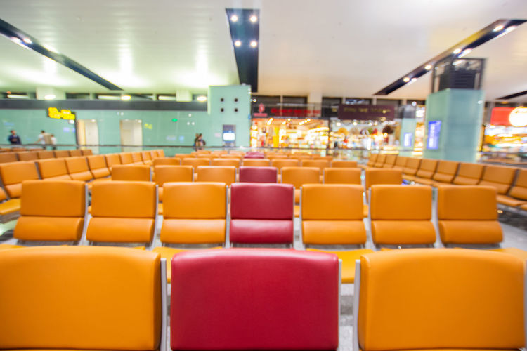 Seat Chair In A Row Indoors  Illuminated Absence Empty Orange Color No People Arrangement Focus On Foreground Ceiling Repetition Large Group Of Objects Side By Side Transportation Airport Multi Colored Order