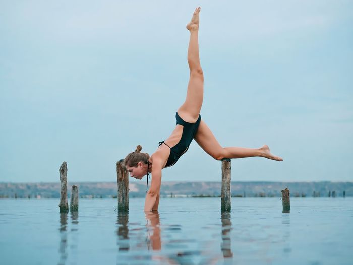 Exercising Balance Practicing Concentration Yoga Lifestyles Leisure Activity Vitality Flexibility Water Handstand  Healthy Lifestyle Full Length Day Real People Outdoors Nature One Person Skill  Young Women