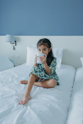 Portrait of girl sitting on bed at home
