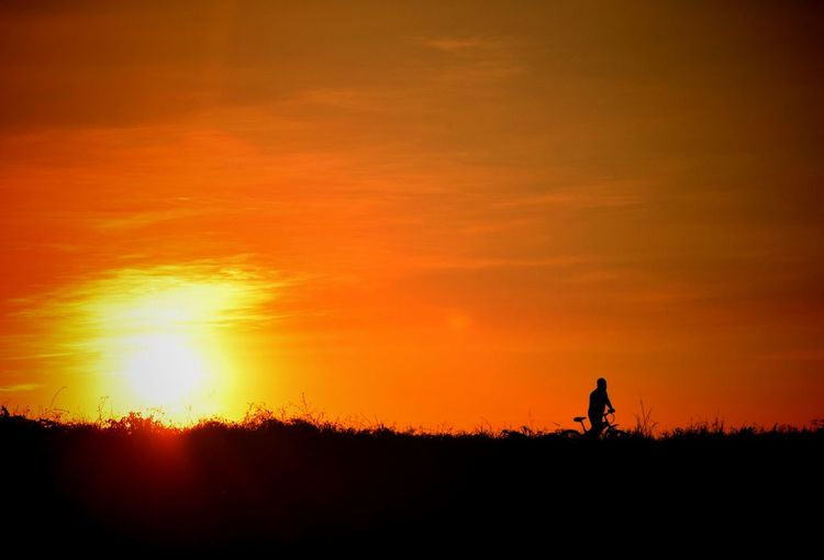 Silhouette Man Riding Bicycle On Field Against Orange Sky