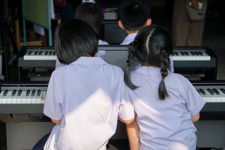 Back portrait of two girls in student uniform playing same electrical piano together in event. Rear View Musical Instrument Piano Key Hairstyle Playing Piano Two People Togetherness