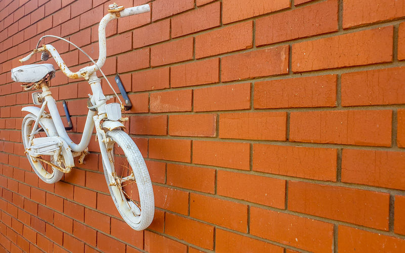 Close-up of bicycle on brick wall