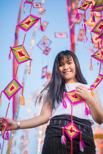 Portrait of smiling woman holding colorful decorations
