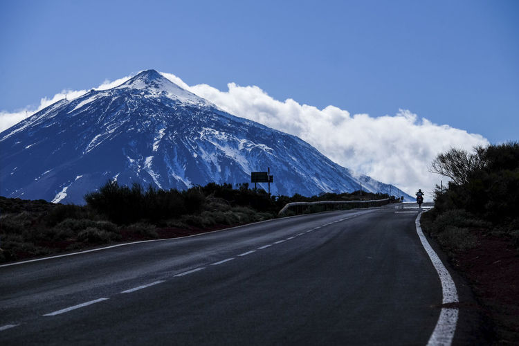 Road by snowcapped mountains against sky