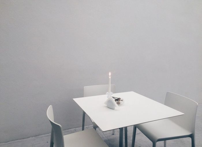 Lit candle on table by empty chairs against wall