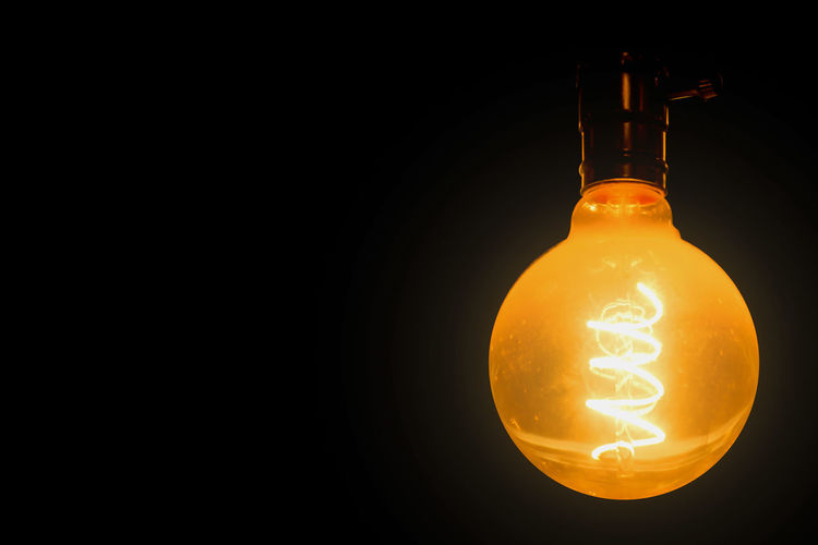 Light Bulb Illuminated Glowing Filament Black Background Studio Shot Lighting Equipment Copy Space Electricity  Indoors  Electric Light Single Object Light Yellow No People Orange Color Close-up Dark Light - Natural Phenomenon Glass - Material Electrical Equipment Luminosity Electric Lamp Power Supply