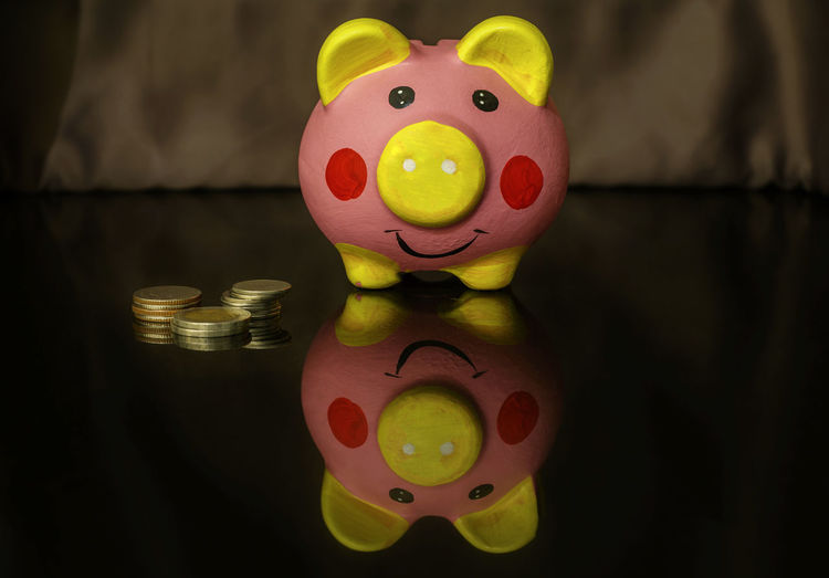 Close-Up Of Coins And Piggy Bank On Table