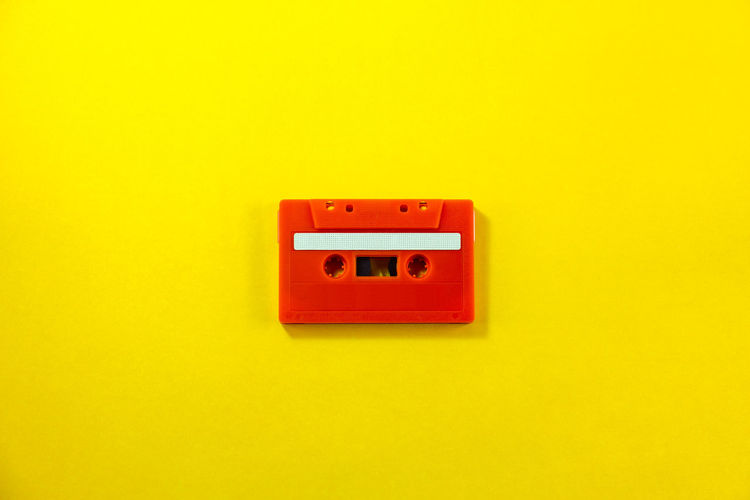 Top view of red classic tape cassette against yellow isolated background. Tape Cassette Music Song Sing Musical Listen Radio Red Audio Sound Record Old Yellow Disco Stereo Media Karaoke Rock Retro Design Vintage Background Headphones Compact Party Blank Play Creative Colorful Pastel Overhead Dance Minimalism Minimal Classic Copy Track Mix Top View Playlist Concept Player Analogue Broadcasting Isolated Broadcast Label Obsolete Plastic The Minimalist - 2019 EyeEm Awards