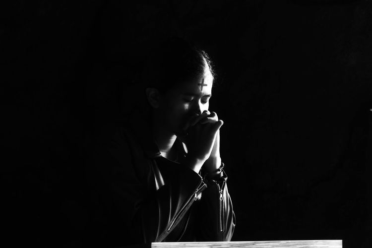 Woman praying while sitting against black background