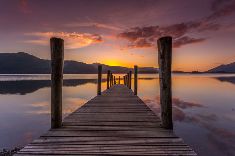 Setting sun over Derwent Water in the Lake District National Park Beauty In Nature Cloud - Sky Day Jetty Lake Mountain Nature No People Outdoors Pier Reflection Scenics Sky Sunset The Way Forward Tranquil Scene Tranquility Water Wood - Material Wood Paneling
