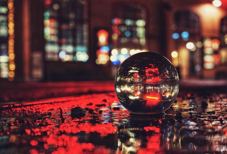 Close-up of illuminated crystal ball in city at night