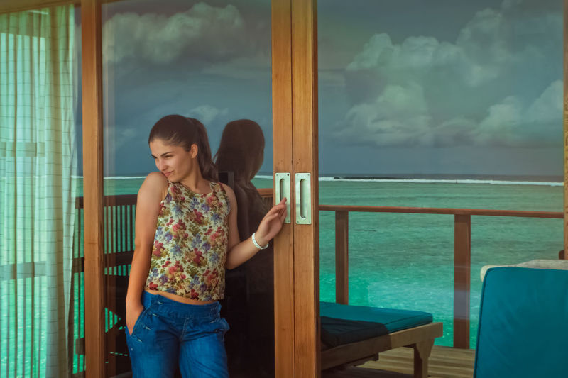 Beautiful woman standing by patio door with reflection of sea
