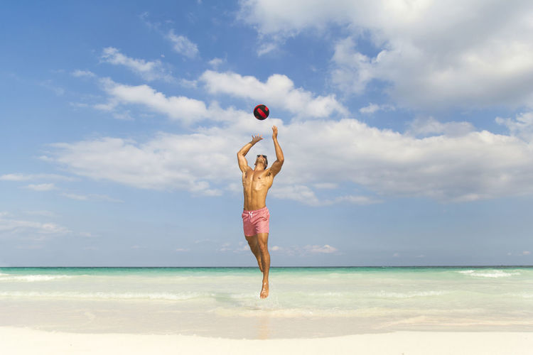 Fit Shirtless Young Man Playing With Ball While Jumping Over Sea Shore Against Sky