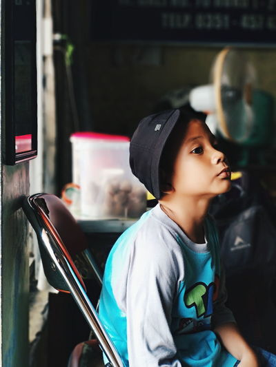 Portrait of boy looking away while sitting in bus