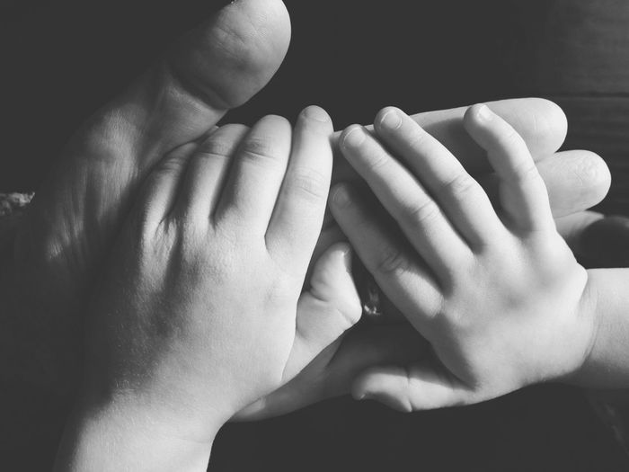 Cropped image of baby holding father hand at home