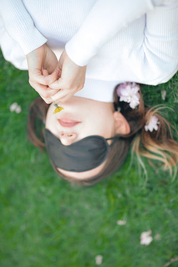 High angle view of woman wearing sleep mask while holding flower on land