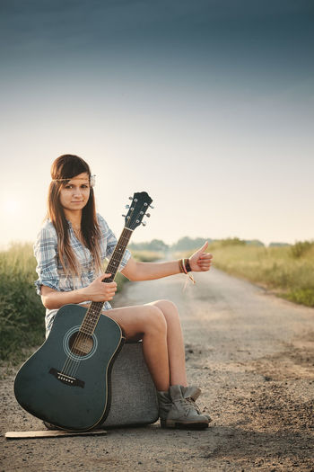 Young woman sitting on guitar