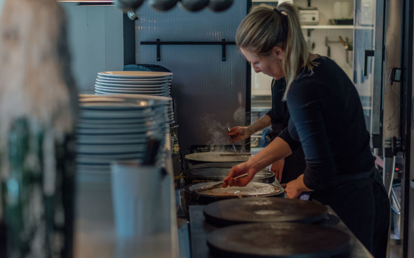 Pancakes being prepared in the cafe kitchen Crêperie Crêpes Woman Blond Hair Commercial Kitchen Day Food Food And Drink Food And Drink Establishment Freshness Indoors  Occupation One Person Pancakes People Preparation  Preparing Food Real People Side View Standing Working