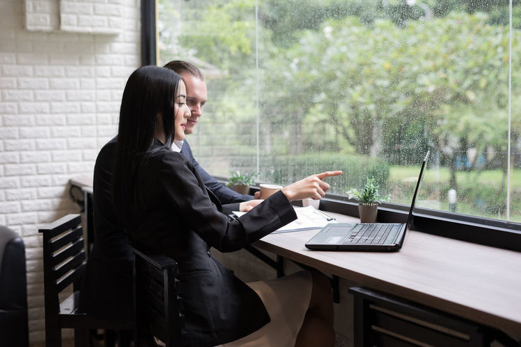 Business Colleagues Discussing Over Laptop At Desk In Office