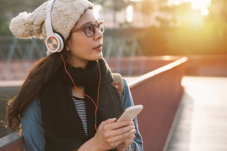 Close-Up Of Young Woman Listening To Music On Footpath