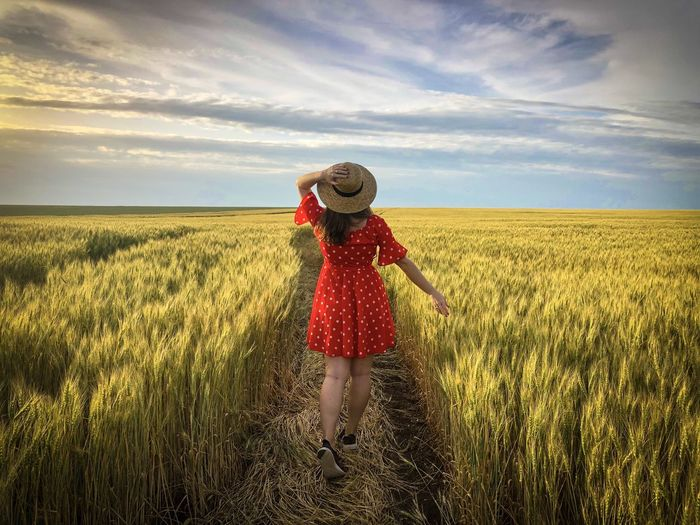 Rear view of woman wearing a red dress and a straw hat standingin a wheat field