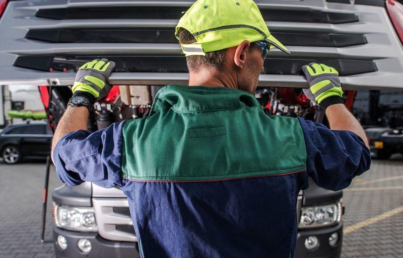 Rear view of man repairing car in garage