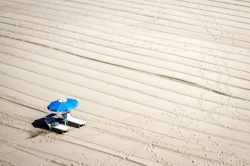 High angle view of lounge chairs with umbrella on sand