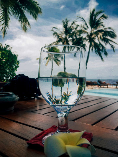 Close-up of wine glass on table against sky
