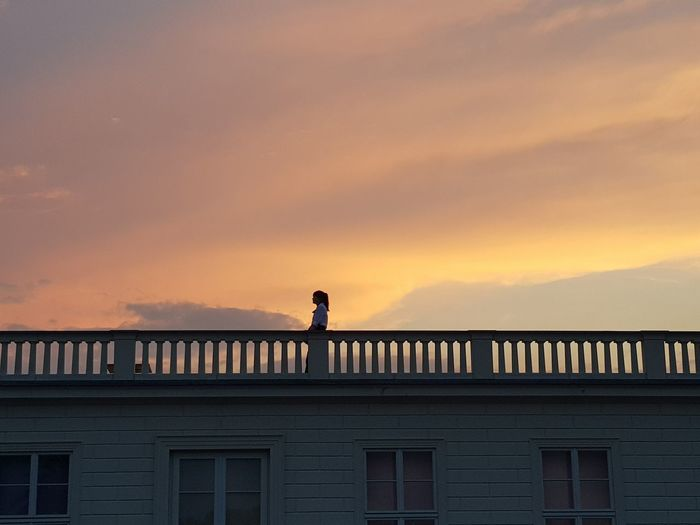 Low angle view of woman standing in balcony against sky during sunset