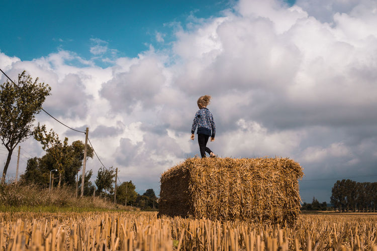 Low Angle View Of Girl Walking On Hay Bale At Farm Against Cloudy Sky