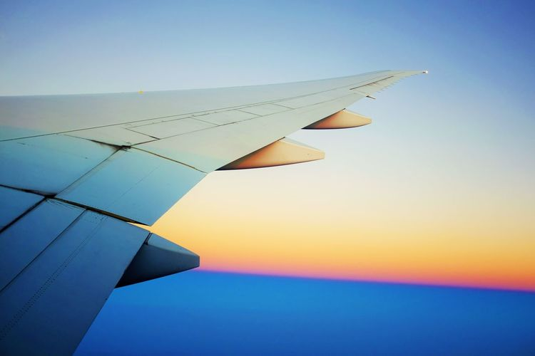 Cropped image of aircraft wing against sky during sunset