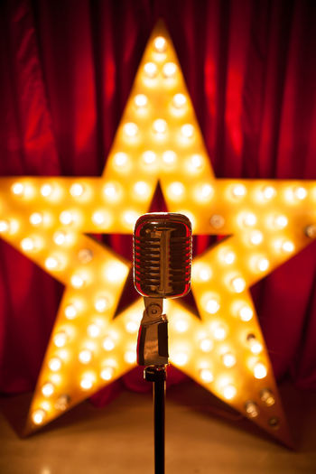 Close-up of microphone against illuminated light bulbs on star shape over stage