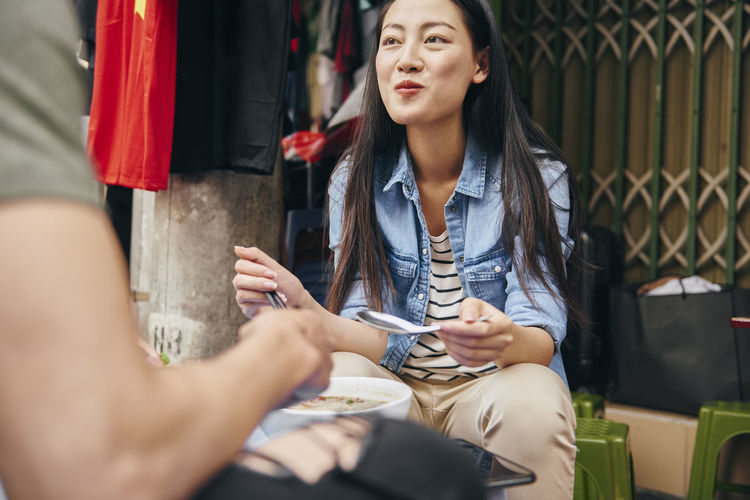 Smiling woman eating food while sitting outdoors