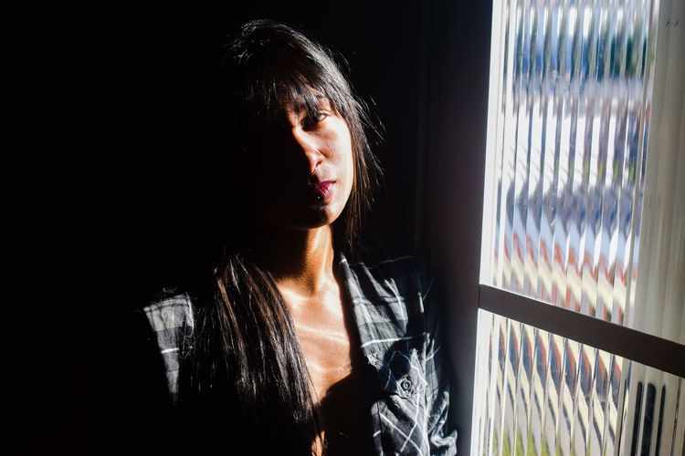 Portrait Of Young Woman Standing By Window At Home