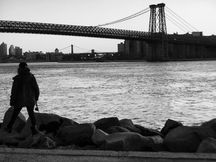 Rear view of silhouette person in front of williamsburg bridge over east river
