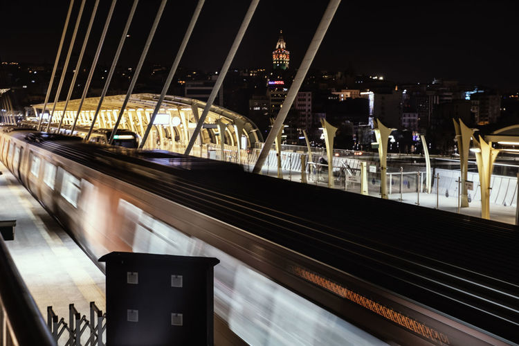 Architecture Built Structure Night Transportation Illuminated Rail Transportation Building Exterior Motion No People Railing Mode Of Transportation City Blurred Motion Connection Railroad Station Bridge Outdoors High Angle View Train Public Transportation Modern Track The Art Of Street Photography