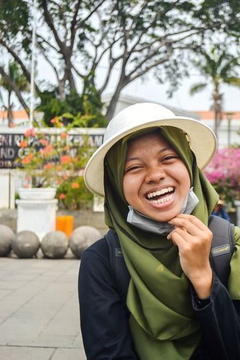 Portrait of a smiling young woman with a white bucket hat