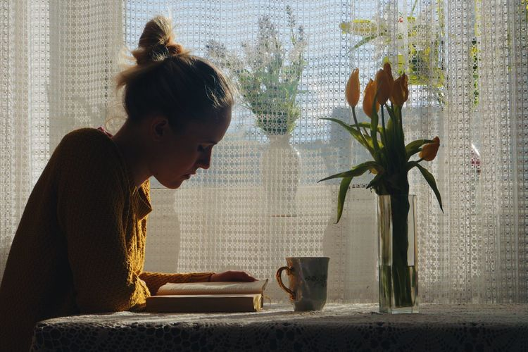 caucasian woman reading book and having tea at home Window Afternoon At Home Book Break Coffee Cozy Cup Girl Indoors  Leisure Activity One Person People Reading Relax Relaxation Rest Tea Tea Time Woman