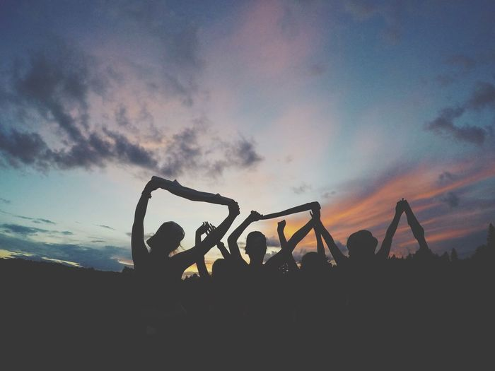 Friends enjoying against sky during sunset