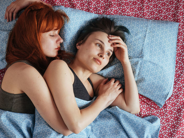 Lesbian woman with girlfriend lying on bed at home