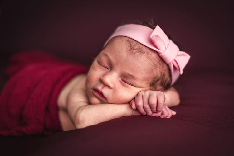 A newborn baby girl with a headband sleeping peacefully. newborn session concept