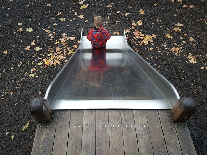 High angle view of boy on slide during autumn