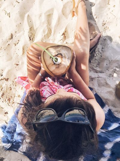 Directly above shot of woman holding coconut at beach