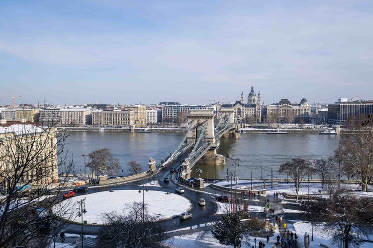 Bridge over river in city during winter
