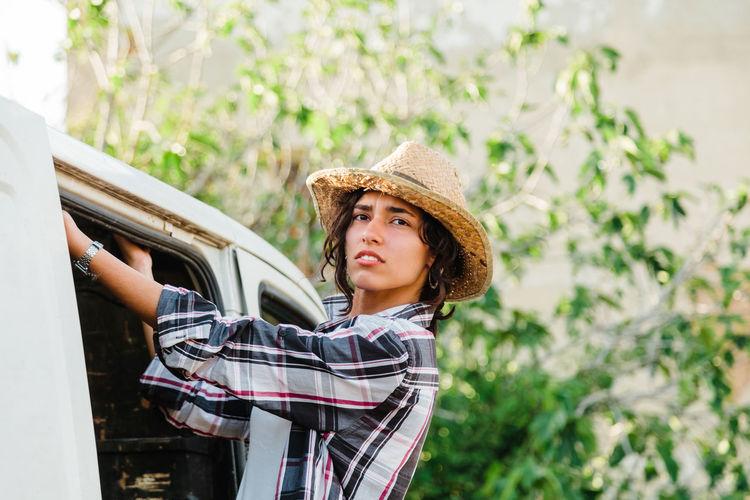 Portrait of young woman standing by motor van